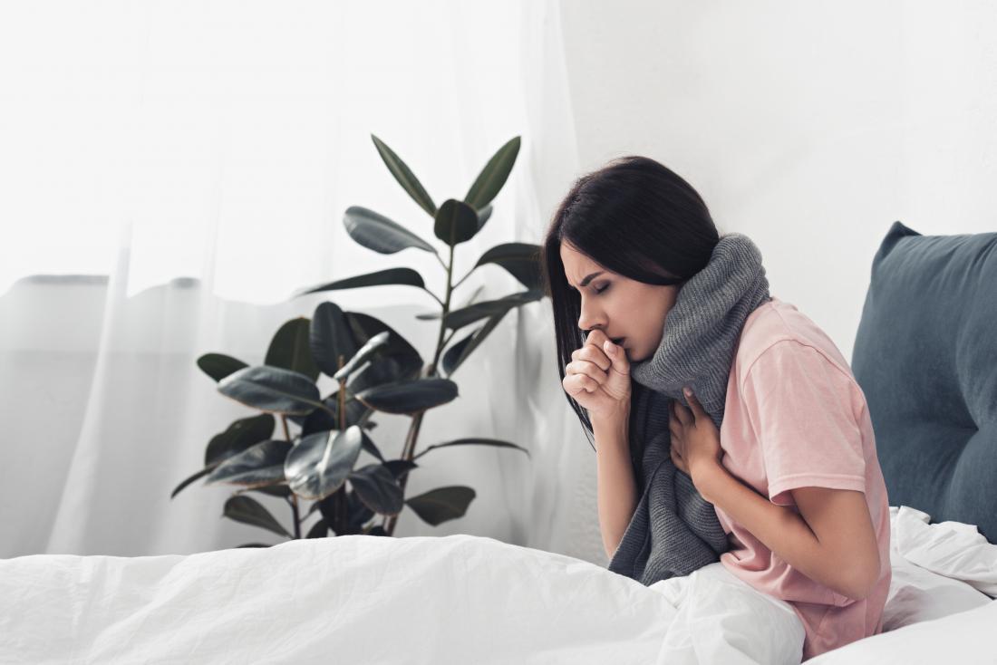 Woman sat up coughing due to chronic laryngitis