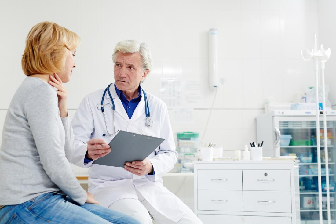 Doctor with patient holding throat in pain
