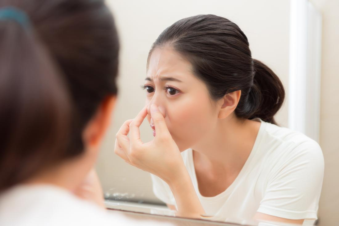 Woman inspecting her nose in mirror