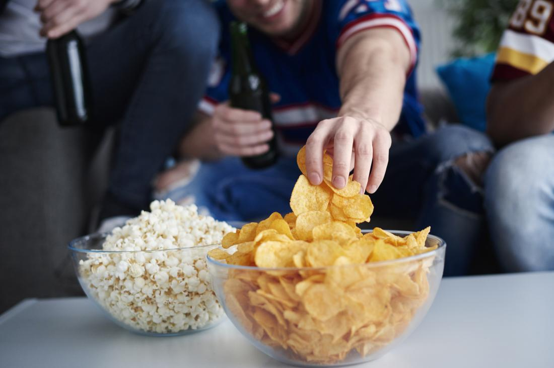 Group of people at home, drinking and eating popcorn and crisps out of bowls.