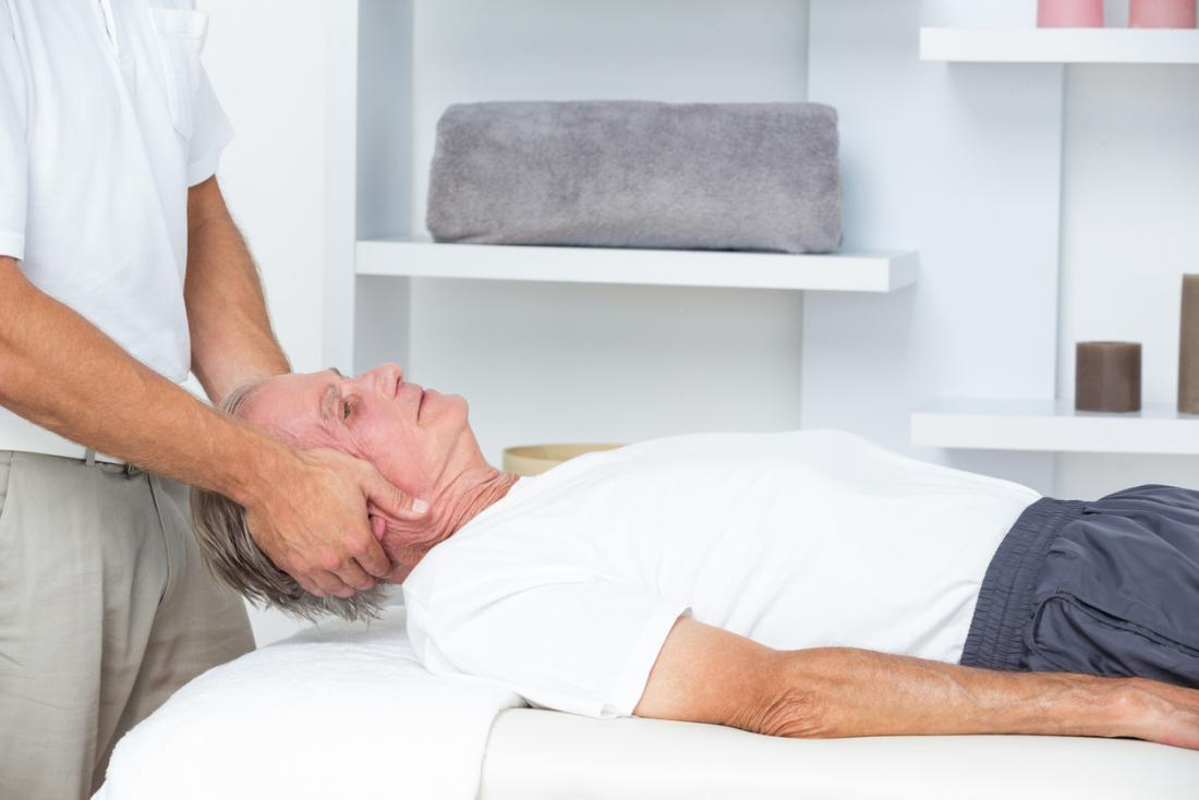 Senior man receiving head and neck massage from chiropractor.