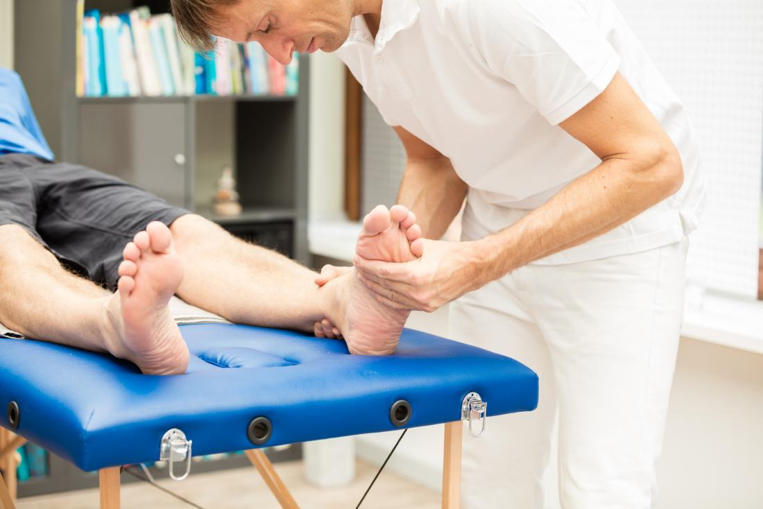 Podiatrist inspecting patient's feet.