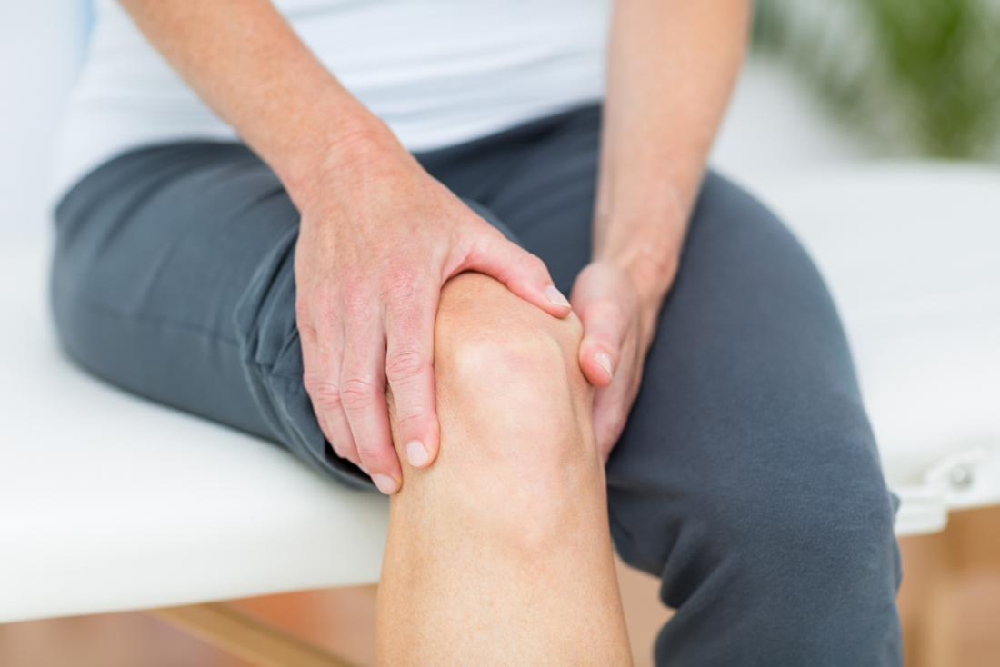 Person experiencing joint pain in their knee.
