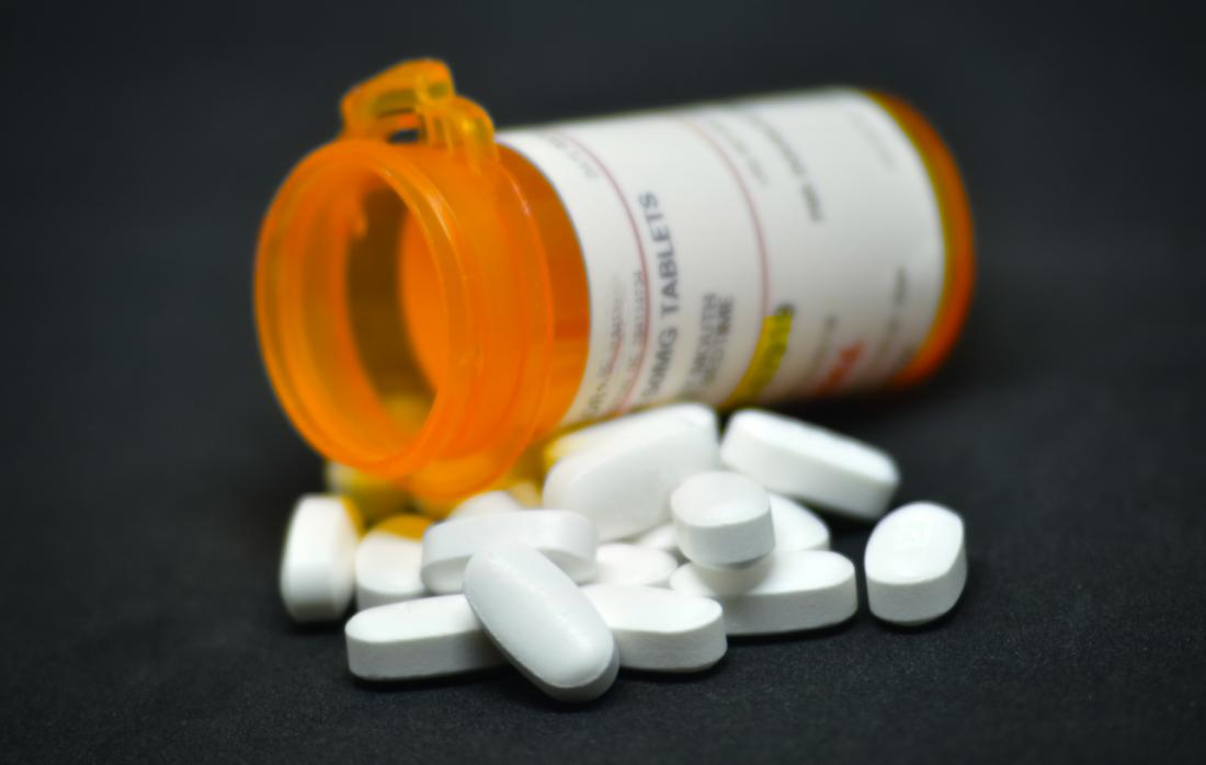 Bottle of pain killer medication, with pile of pills in the foreground.