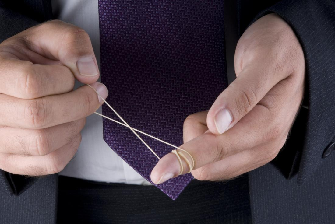 Man in business suit wrapping elastic band around finger.