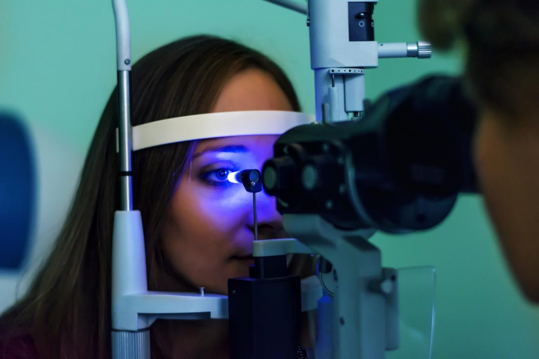 Woman having eye exam or test at optician