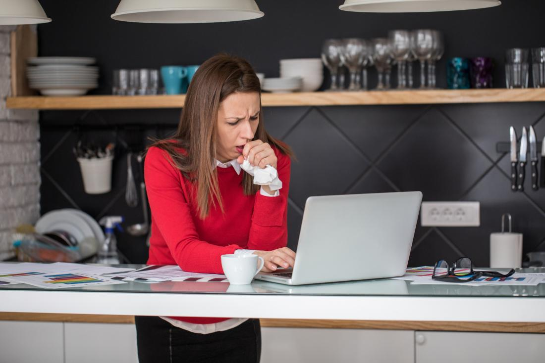 Woman coughing while working from home on laptop