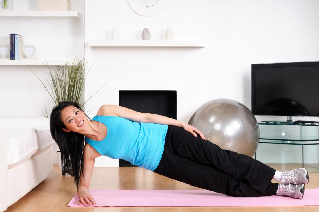 A lady performing the side plank exercise in her home