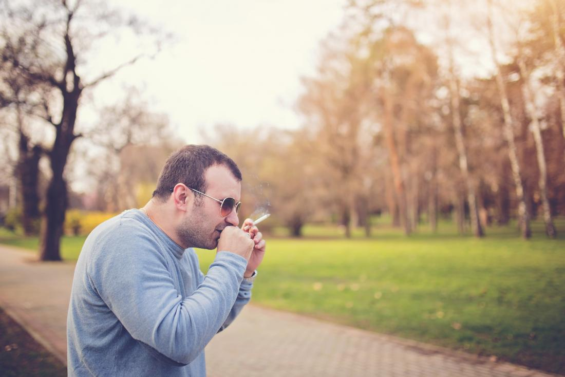 man smoking in a park and coughing