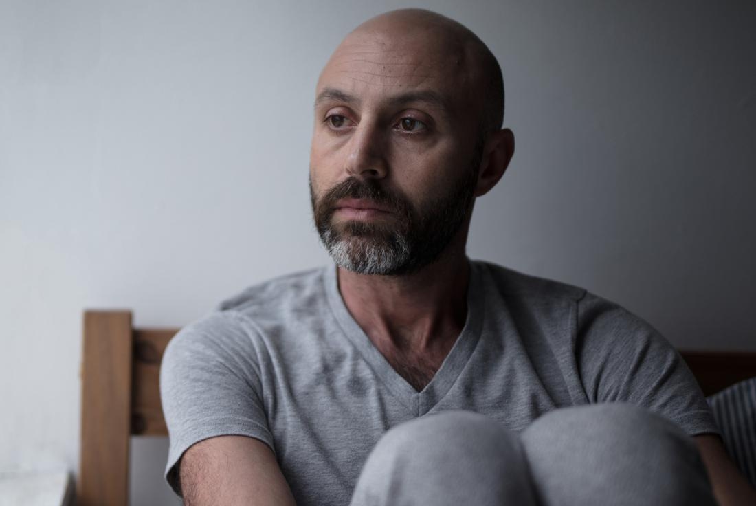 Man sitting on bed hugging knees looking depressed