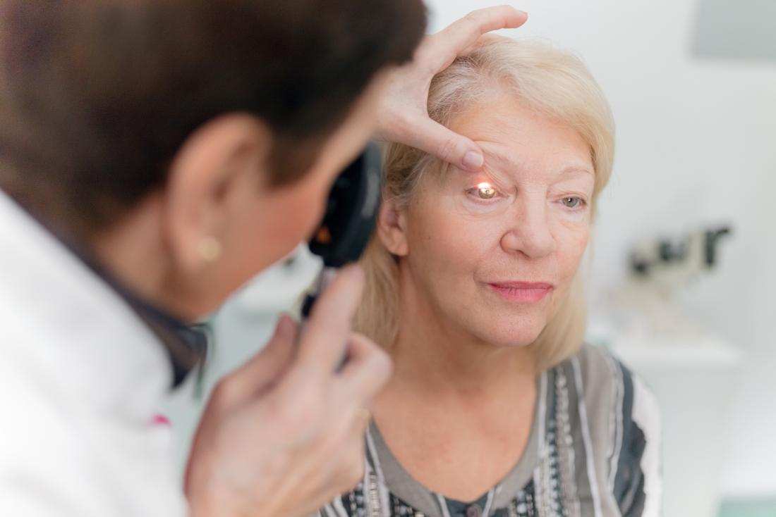 optician using an ophthalmoscope to inspect mature woman s eye