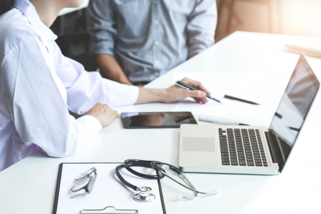 Doctor explaining something to patient at desk with various devices on it