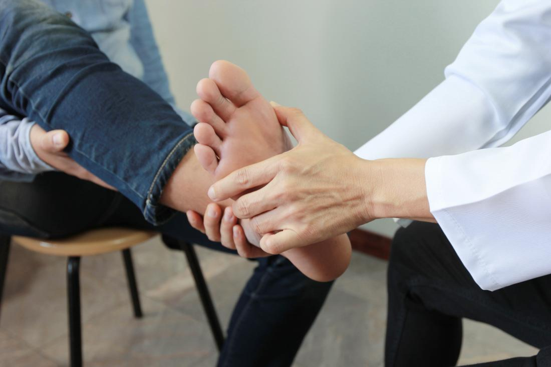 Doctor or podiatrist checking patients bunion on foot