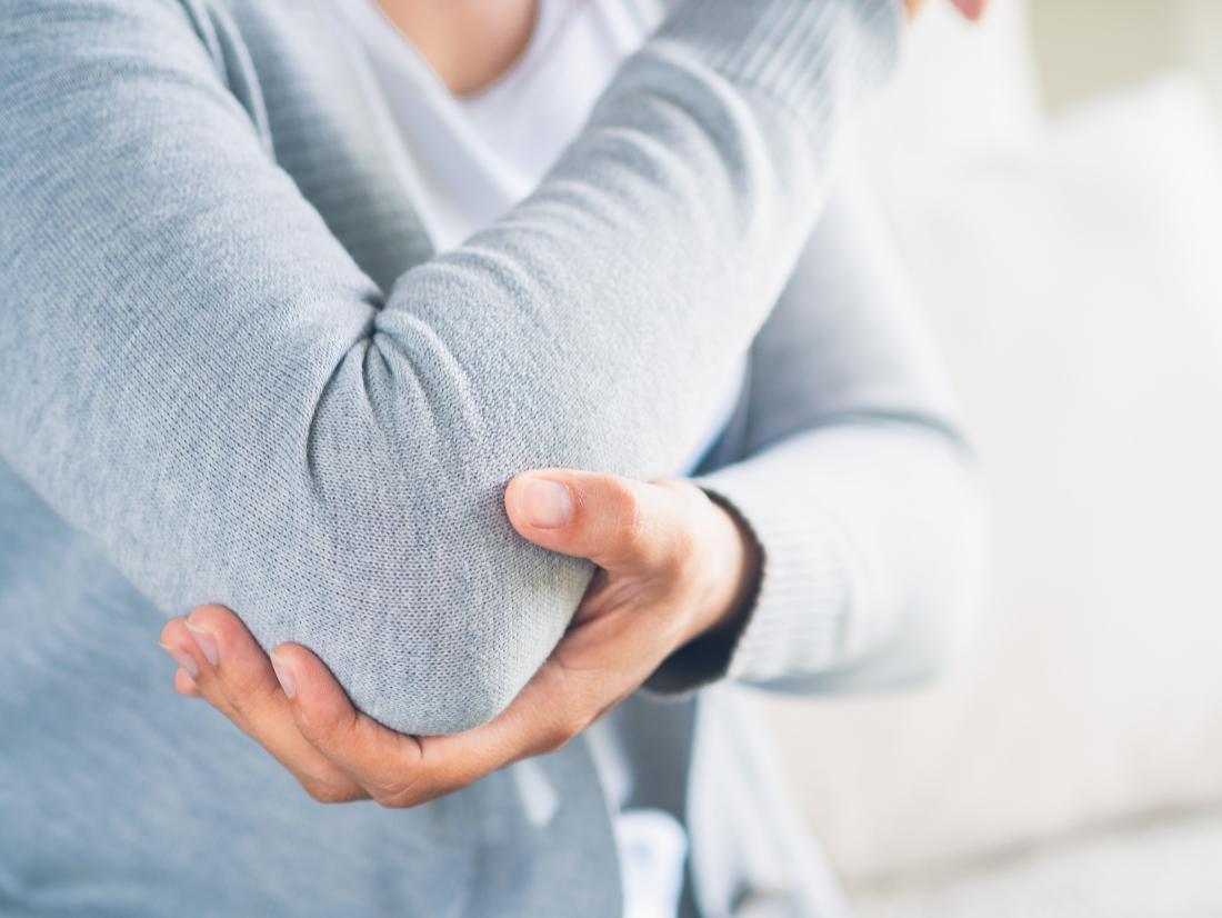Holding elbow in pain due to Rheumatoid Arthritis or Osteoarthritis