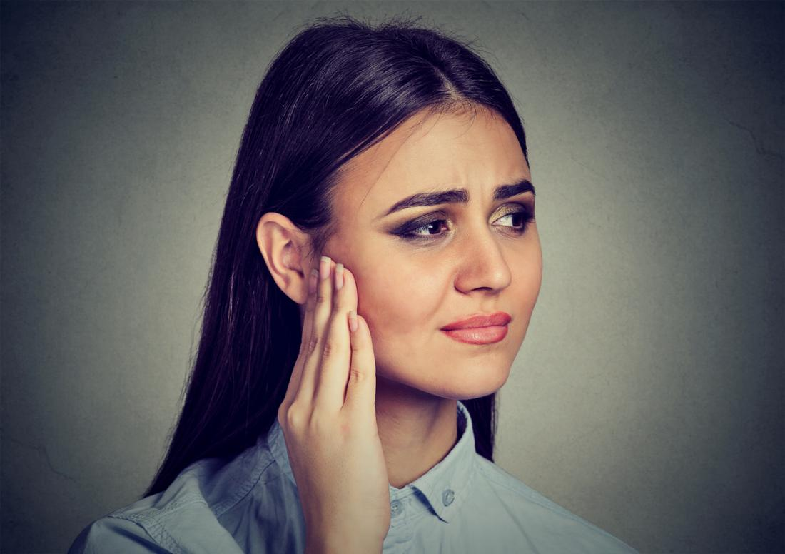 Woman touching her ear, looking pained.