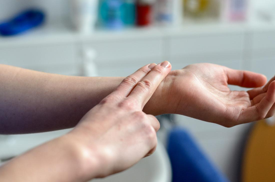 Woman checking her pulse by placing two fingers on her wrist.