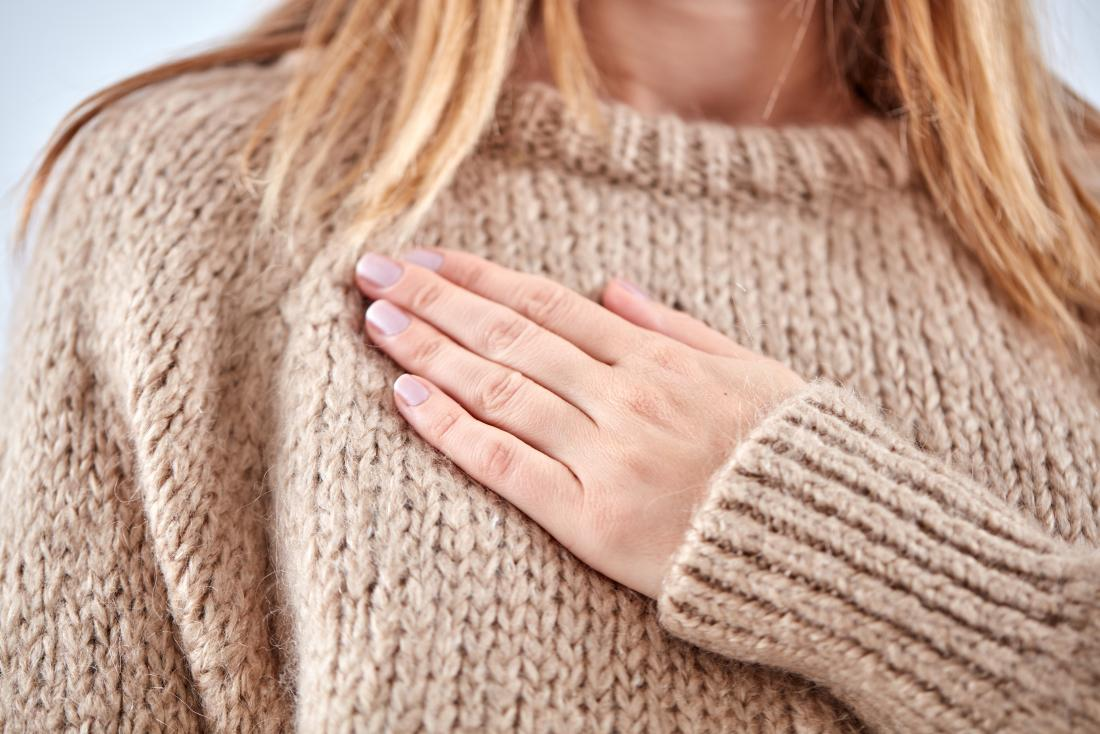 Woman with sore breast pain holding hand over chest