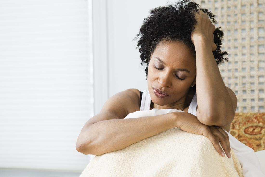 Tired woman holding head because of diabetes fatigue
