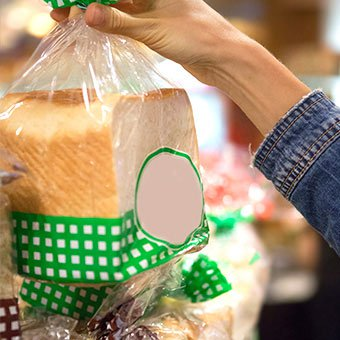 A person holds a bag of sliced white bread.