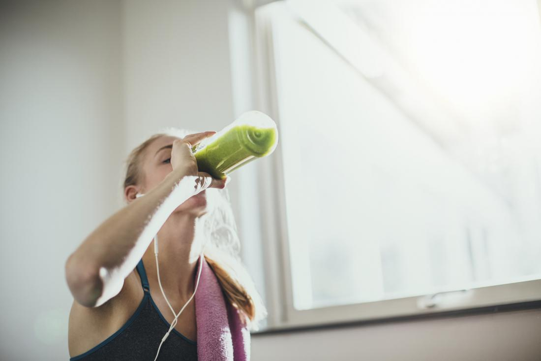 woman drinking smoothie after exercising