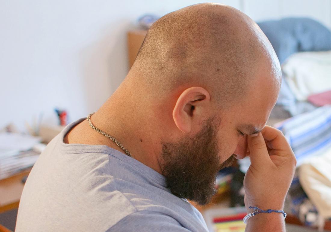 Bald man experiencing headache and stress pinching bridge of nose.