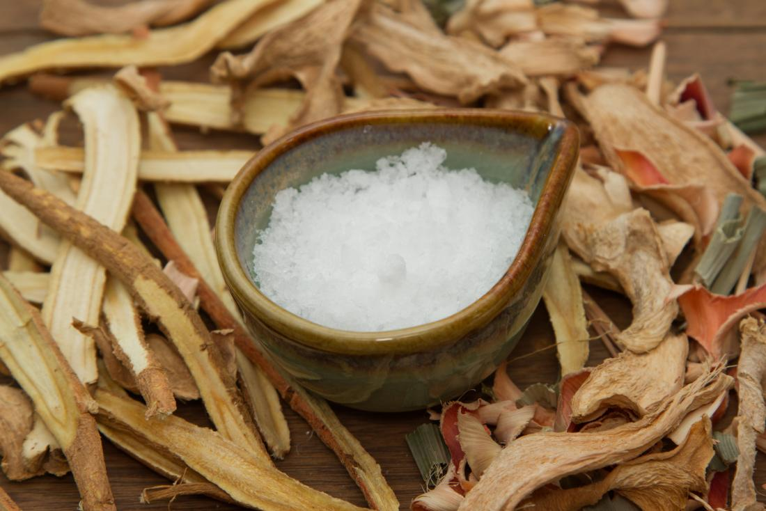 Camphor in a bowl amongst roots and plants on wooden table