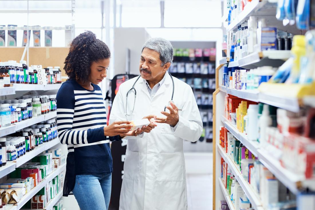 Woman in pharmacy speaking to pharmacist about medication