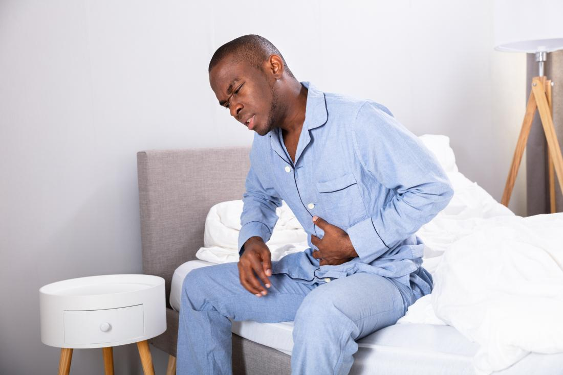 Man holding stomach in pain due to duodenal cancer