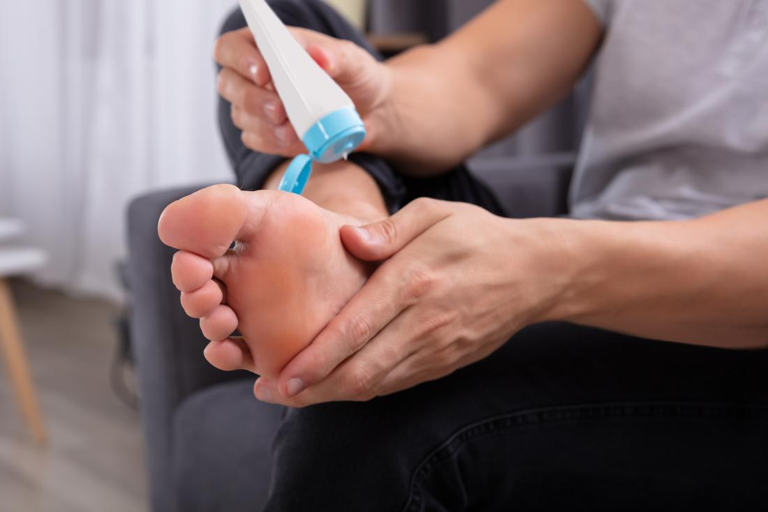 Man applying cream to his foot