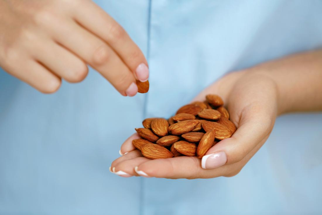 close up of womans hand full of almonds