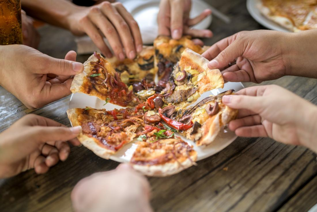 close up of hands dividing pizza