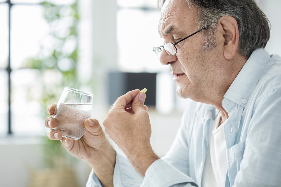 Senior man taking supplements with glass of water