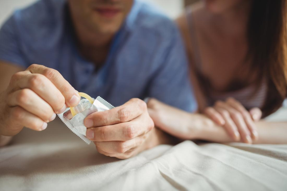 couple on bed with man removing condom from package