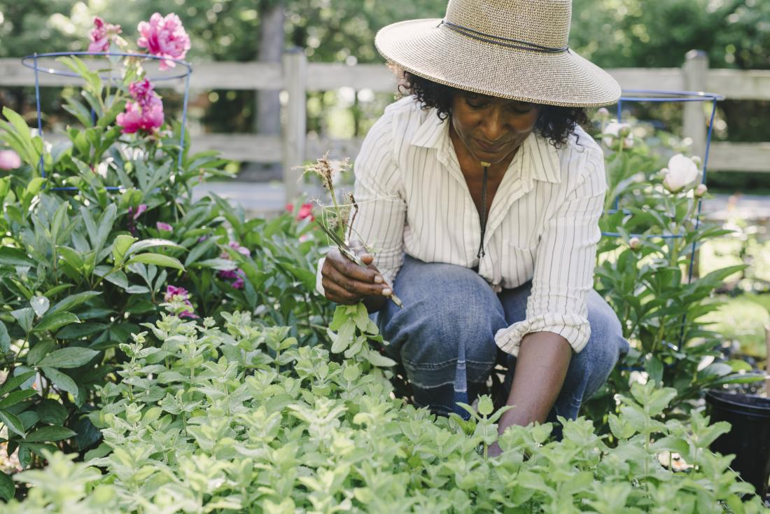 Woman outdoors gardening with sun hat on.