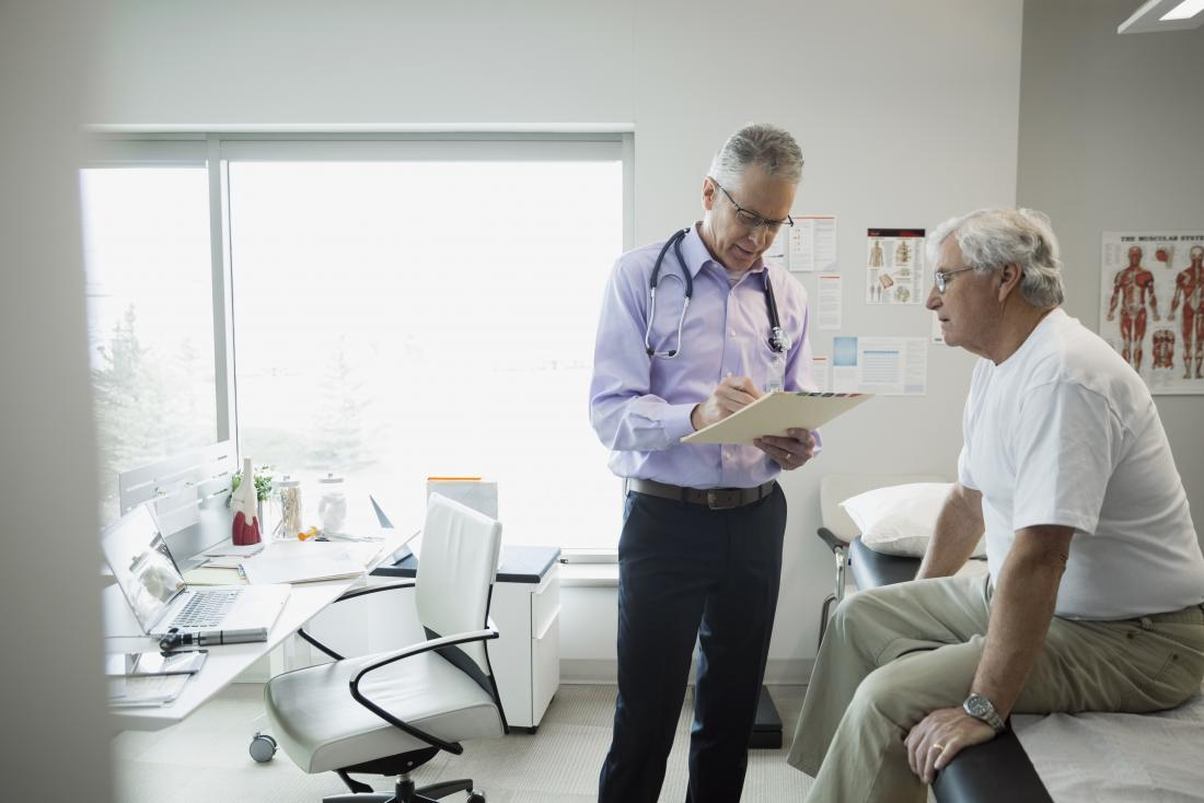 Mature male patient sitting on bed in doctor's office while he looks like clipboard