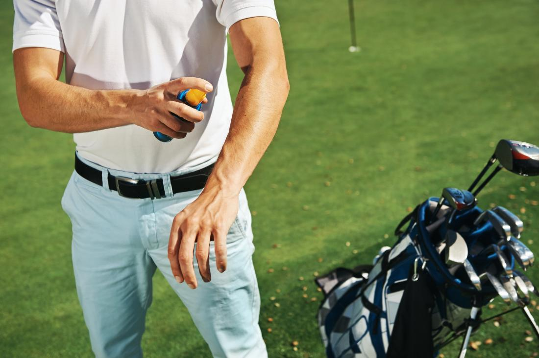 male golfer spraying sun protection on arm
