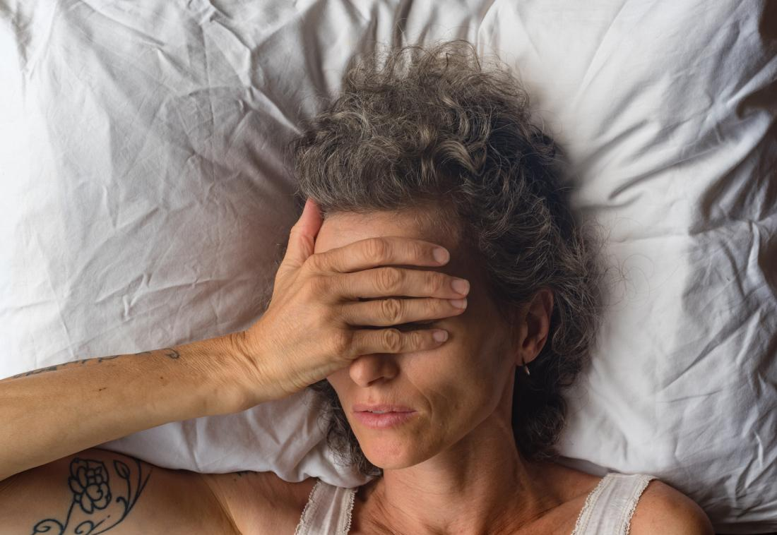 middle aged woman covering her eyes