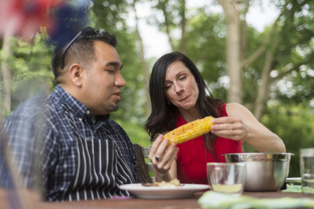 People eating corn on the cob at outdoor BBQ
