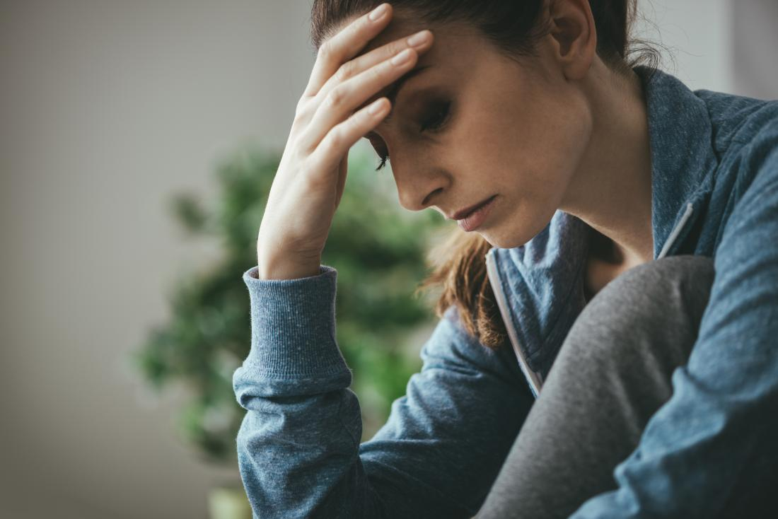 woman with endometrial fatigue holding head and looking tired and sad