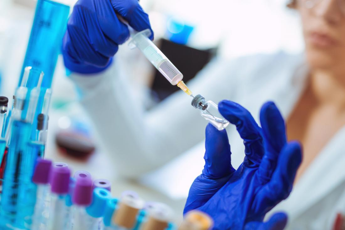 researcher with experimental vaccine