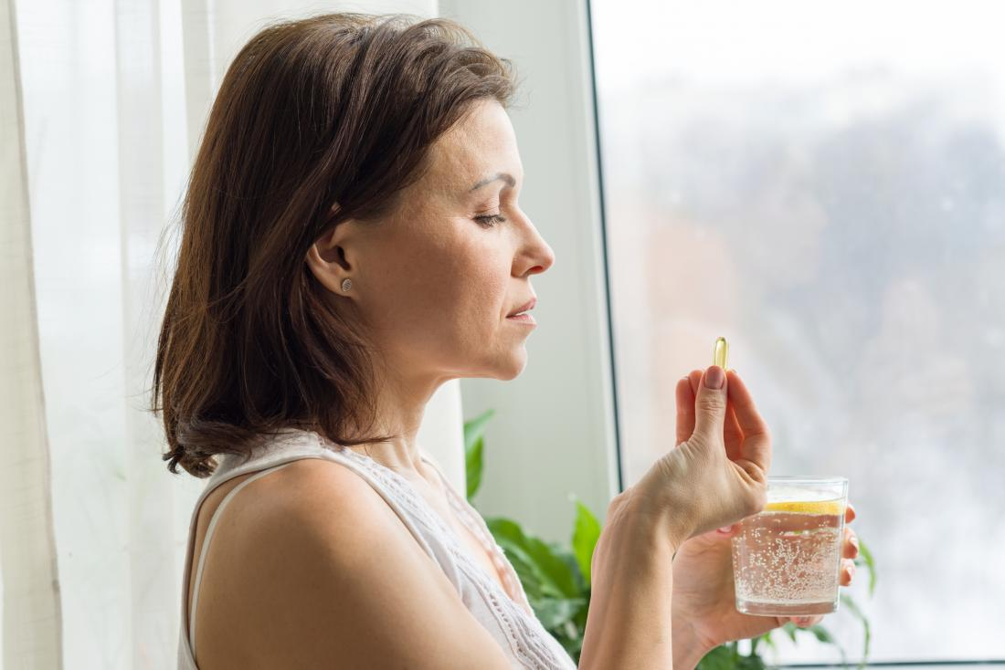 Woman taking dietary supplement with glass of water.
