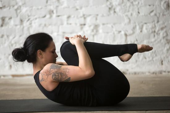 Back flexion stretch as woman on yoga mat hugs her knees to her chest