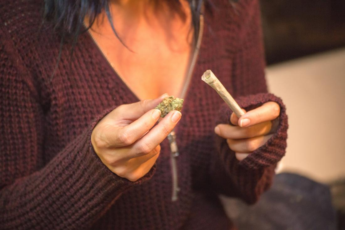 Woman holding marijuana bud and cannabis joint for smoking weed