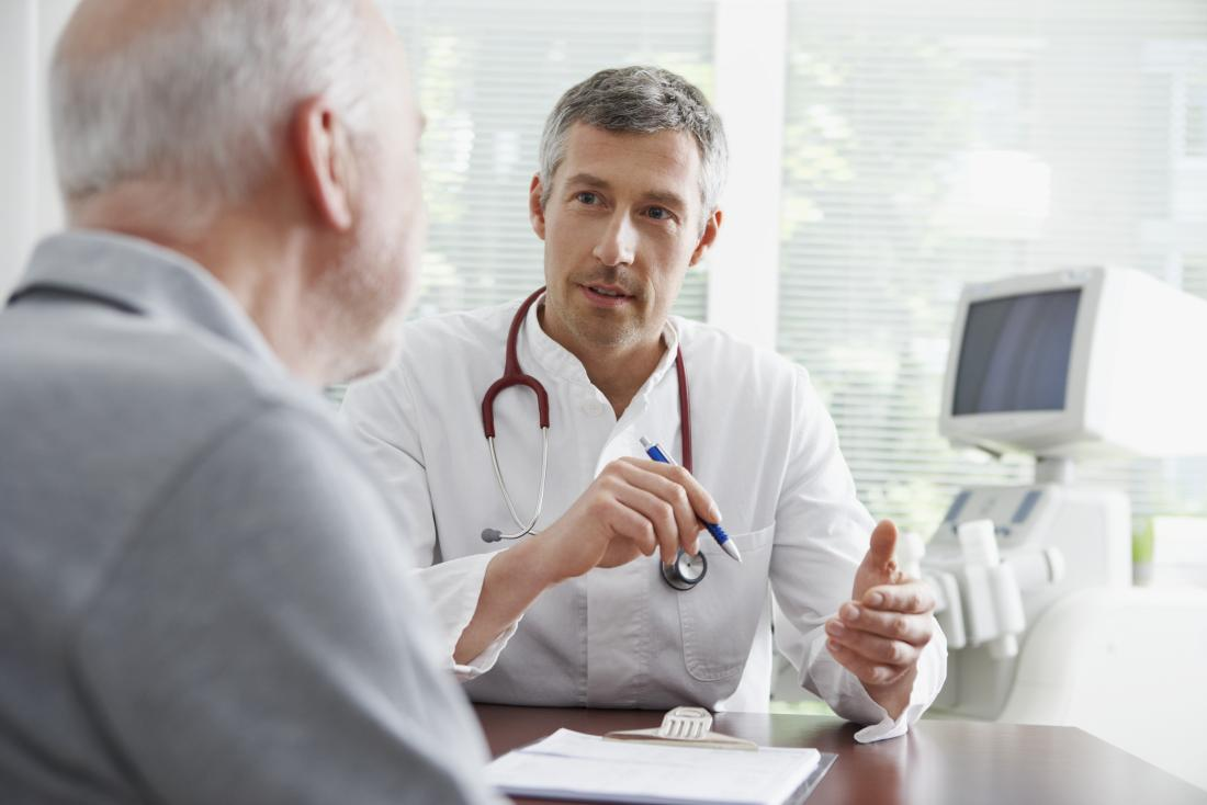 Doctor in office speaking to senior male patient