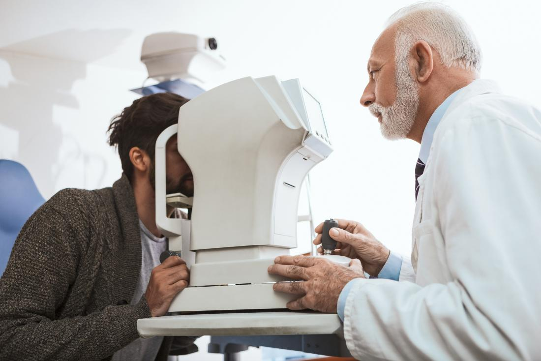 optician or Optometrist with optometry machine checking patient