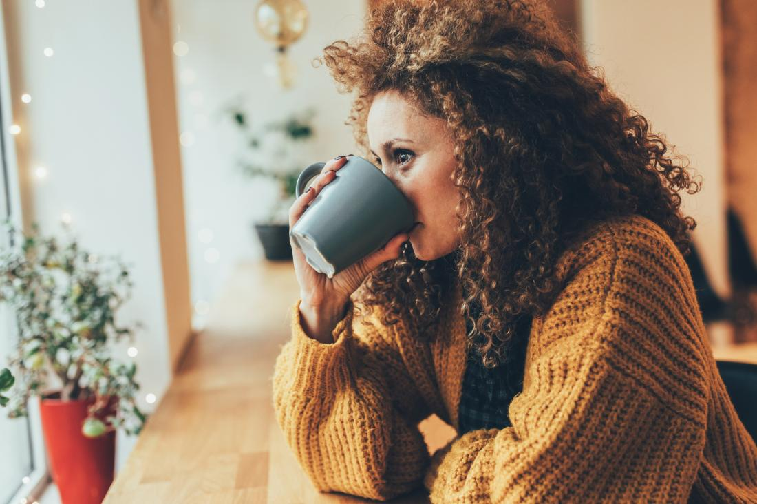 Woman drinking hot drink from mug in cafe.