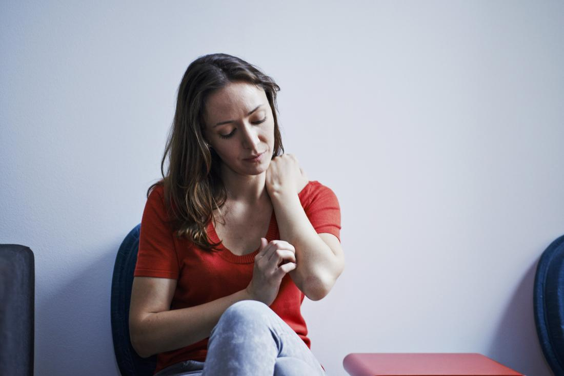 woman sitting in waiting room itching arm