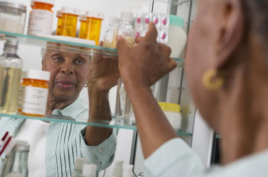 Mature post-menopausal woman reaching for medication in pill bottles in bathroom cabinet.