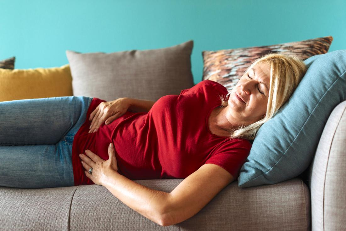 Mature woman with abdominal pain or menstrual cramps lying on side on sofa holding stomach.
