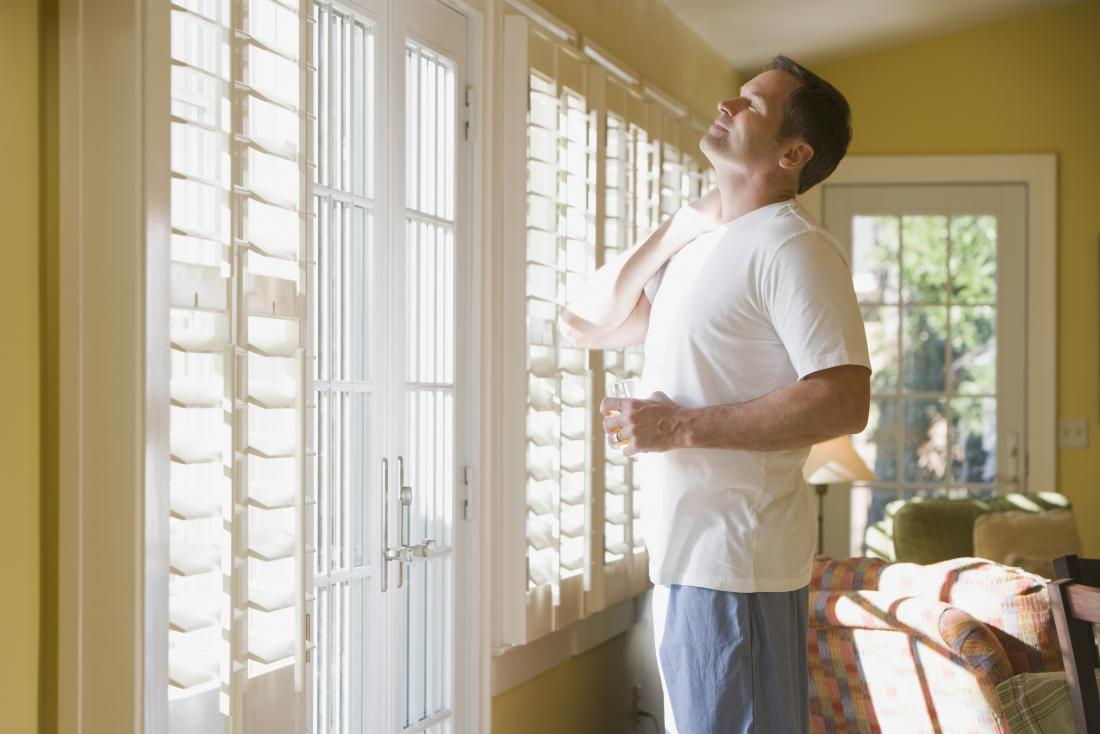 Man standing in house looking out of window having just woken up, holding stiff neck and glass of water.